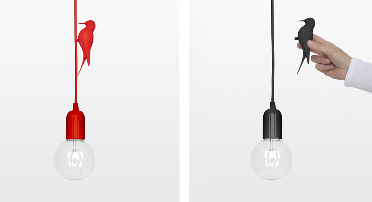 side view of a red 3D printed bird clipped onto a fabric cable of a suspended pendant bulb light hand holding a 3D printed black bird and clipping it onto a fabric cable from a black suspended bulb pendant light